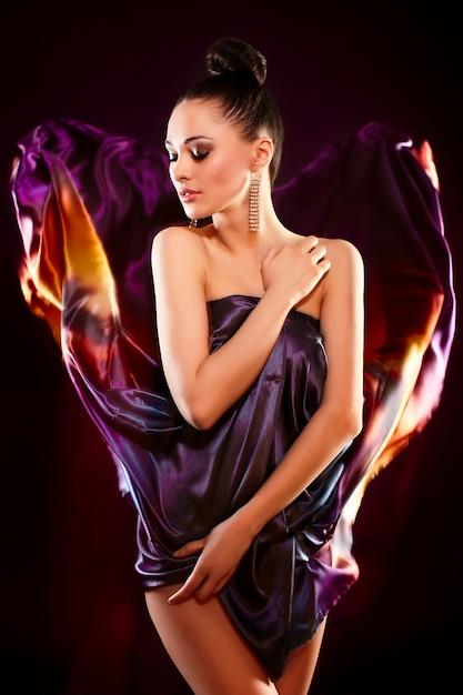 Sensueel manierportret van het mooie sexy donkerbruine meisjesmodel stellen in heldere kleurrijke vliegende kleding, birghtmake-up die op zwarte achtergrond wordt geïsoleerd Gratis Foto