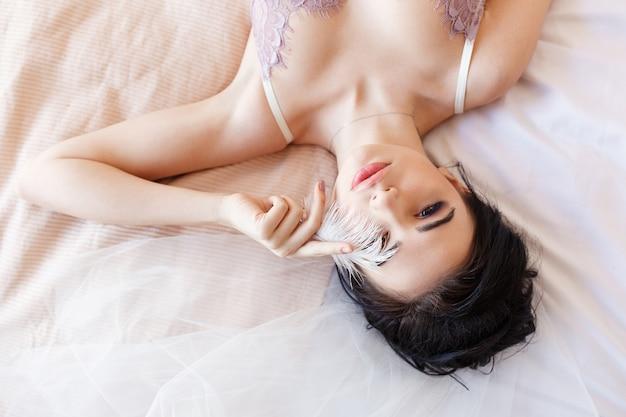 Sensuele donkerbruine mooie vrouw die op bed in witte lingerie liggen die oog behandelen met veer Gratis Foto