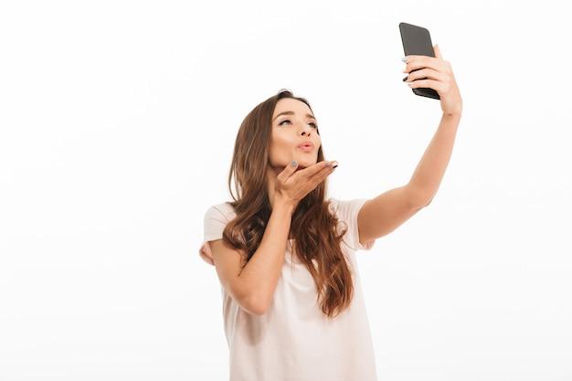Sensuele donkerbruine vrouw die in t-shirt selfie op smartphone maken en luchtkus over witte muur verzenden Premium Foto