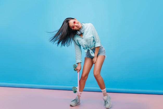 Sensuele donkerharige meisje in casual straat outfit dansen, longboard te houden. spaanse vrouw in sneakers poseren met glimlach vangen. Gratis Foto