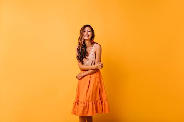 Sensuele goedgehumeurde vrouw poseren in zomerkleren. langharige meisje met schattige glimlach met plezier in de studio. Gratis Foto