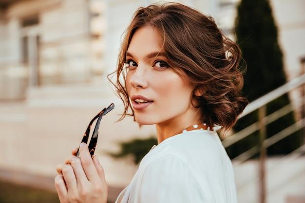 Sensuele jonge vrouw die in witte blouse over schouder kijkt. positieve elegante meisje met kort haar poseren op straat. Gratis Foto