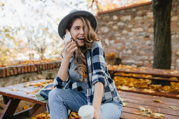 Sensuele krullende vrouw in hoed grappige emoties uitdrukken tijdens fotoshoot in herfst tuin Gratis Foto