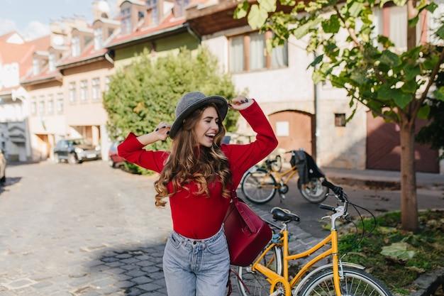 Sensuele langharige meisje in rode trui plezier buiten met fiets Gratis Foto