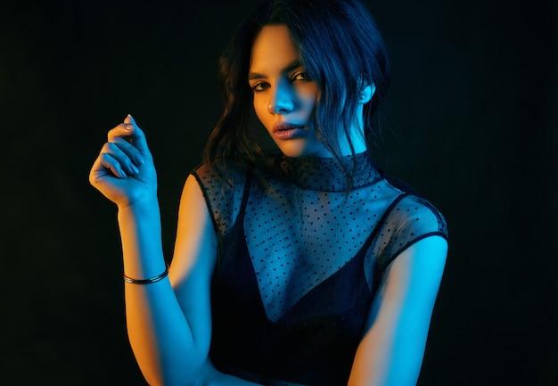 Sensuele mooie brunette vrouw in een sexy mode jurk gekleurd met edelstenen Premium Foto