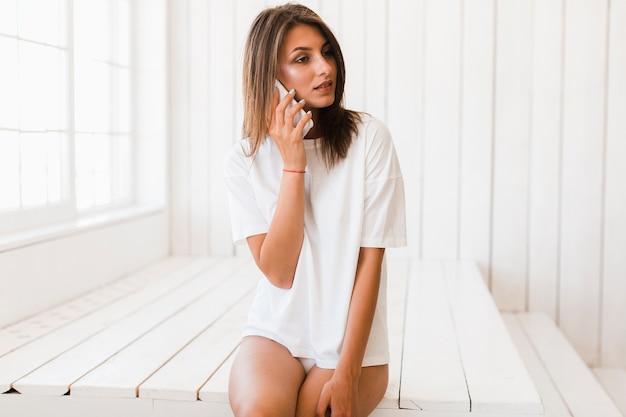 Sensuele vrouw die op telefoon spreekt Gratis Foto