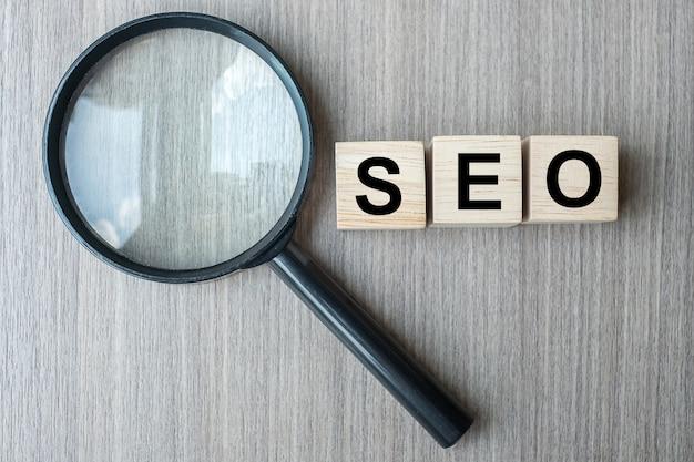 Seo (search engine optimization) tekst houten kubussen en vergrootglas Premium Foto