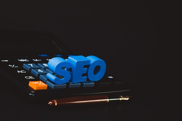 Seo-tekstalfabet voor search engine optimization-concept en kantoorartikelen of kantoorwerk, essentiële gereedschappen of artikelcalculator Premium Foto