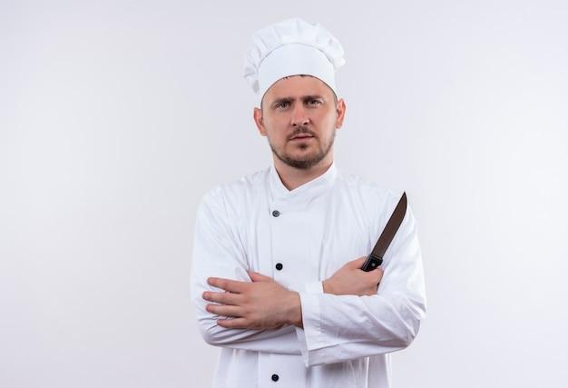 Serieus uitziende jonge knappe kok in uniforme chef-kok staande met gesloten houding en mes geïsoleerd op witte ruimte te houden Gratis Foto