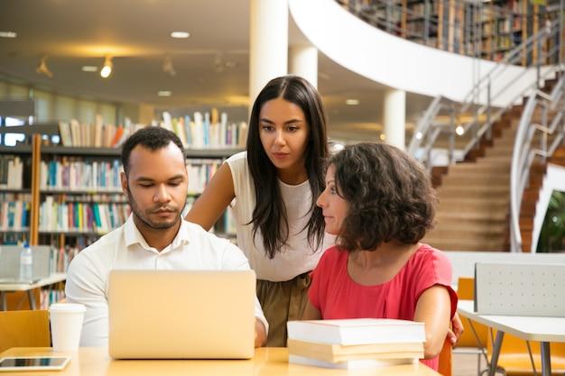 Serieuze studenten zitten aan tafel in bibliotheek werken met laptop Gratis Foto