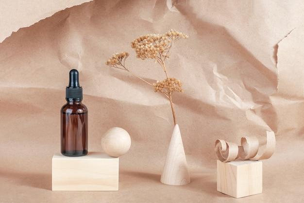Serum, etherische oliën of vloeibaar collageen in bruine glazen fles met pipet, houten geometrische vormen en gedroogde bloemen op beige Premium Foto