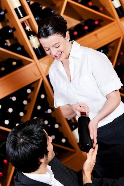 Serveerster biedt een fles rode wijn Premium Foto