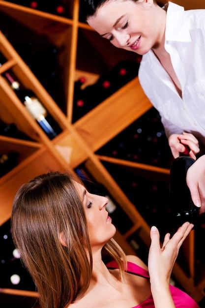 Serveerster in restaurant met rode wijn Premium Foto