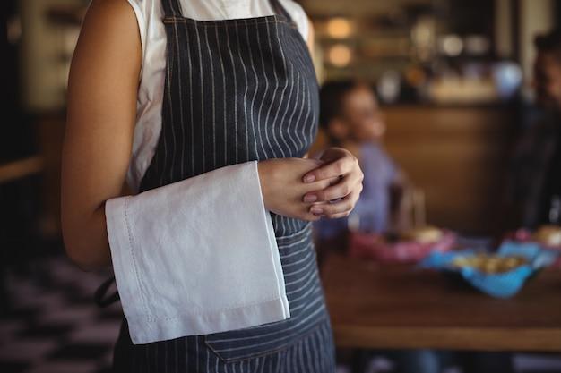 Serveerster met servet dat zich bij restaurant bevindt Premium Foto