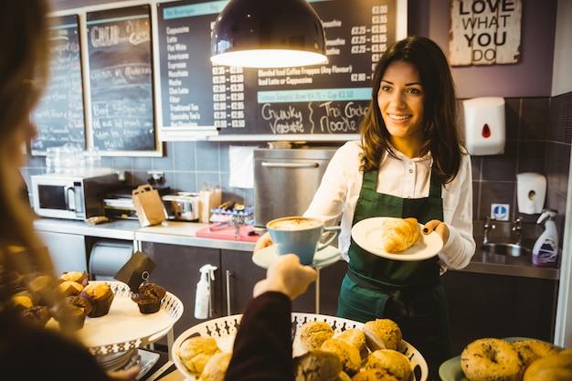 Serveerster serveert een kopje koffie Premium Foto
