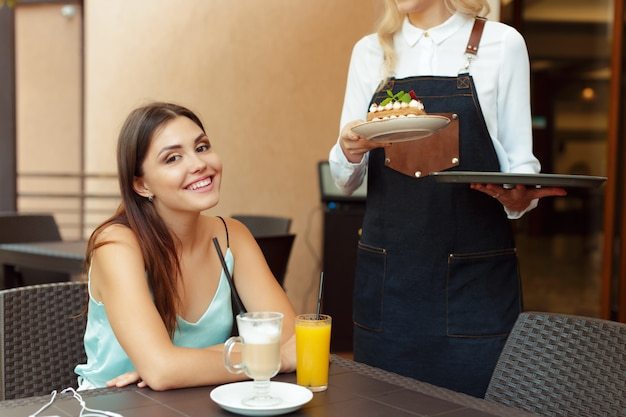 Serveerster server helpt client in café Premium Foto