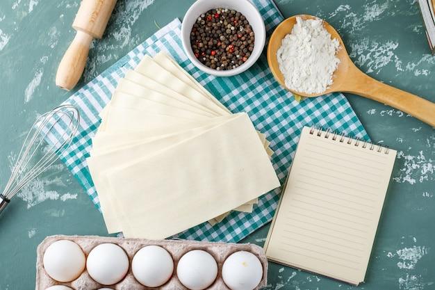 Servetten met eieren, peperkorrels, zetmeel, garde, deegroller en schrijfboek Gratis Foto