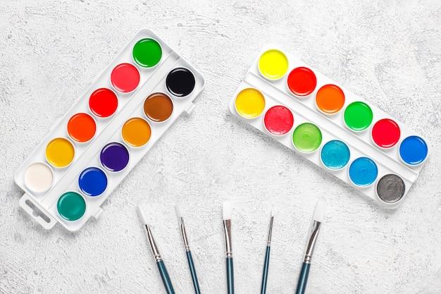 Set aquarel verf en verfborstels om te schilderen. Gratis Foto