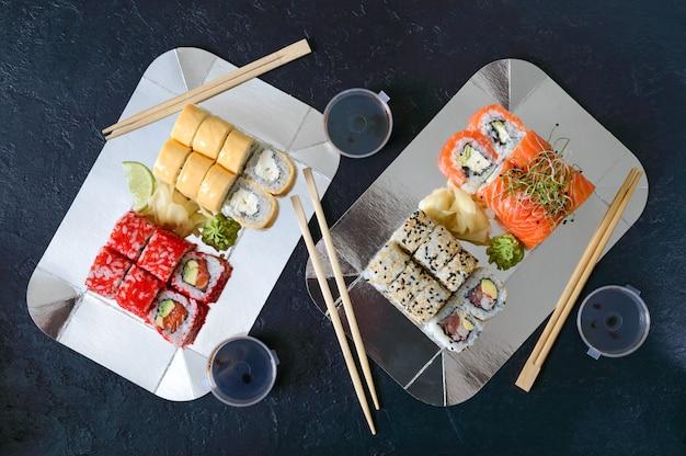 Set sushi rolt, saus, wasabi en hand met stokjes op donkere tafel. sushi restaurant menu. diverse soorten sushi. japans eten. het bovenaanzicht Premium Foto