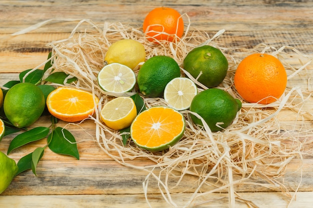Set van bladeren en citrusvruchten op een houten bord Gratis Foto