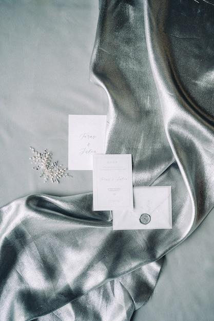 Set van decoratie en bruiloft uitnodiging op een doek met grijze gestructureerde achtergrond. bovenaanzicht. Gratis Foto