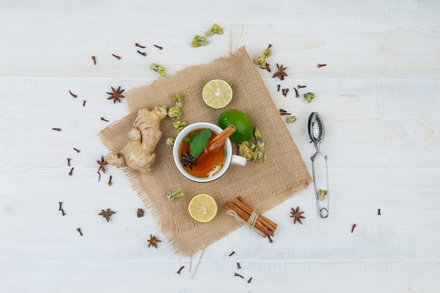 Set van een theezeefje en een kopje thee, limoenen, gember en kaneel in een linnen placemat op een grijze ondergrond Gratis Foto