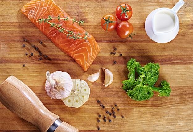 Set van gezonde anti-kanker voedsel op houten tafel. rode zalm vis, broccoli, knoflook, melk, peper en tomaten verspreid over een tafel. gezond maaltijdconcept, hoogste mening Premium Foto