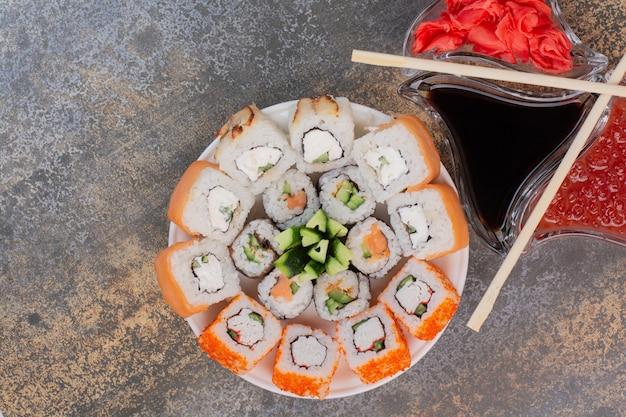 Set van heerlijke sushi met stokjes en gember op marmeren oppervlak Gratis Foto
