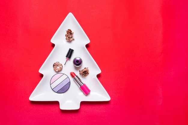 Set van make-up accessoires op cristmas boom, kopie ruimte, rode achtergrond Premium Foto