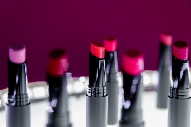 Set van matte lippenstift in rode en natuurlijke kleuren op wit en roze. mode kleurrijke lippenstiften. professionele make-up en schoonheid. knipperende bokeh. Premium Foto