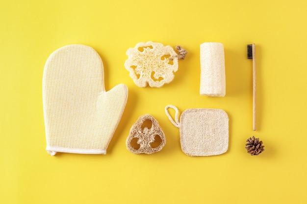 Set van milieuvriendelijke badkameraccessoires, gereedschap voor in bad, natuurlijke bamboe tandenborstel, spons. zero waste cosmeticaproducten op geel. Premium Foto