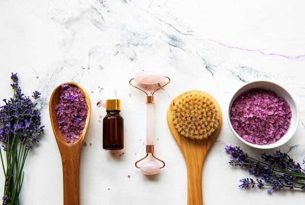 Set van natuurlijke organische spa-cosmetica met lavendel. plat lag badzout, etherische oliën, gezichtsroller, op marmeren achtergrond. huidverzorging, schoonheidsbehandeling concept Premium Foto