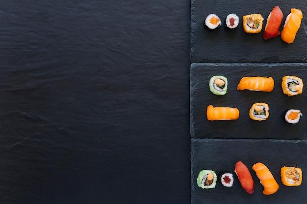 Set van sushi en rollen op planken Gratis Foto