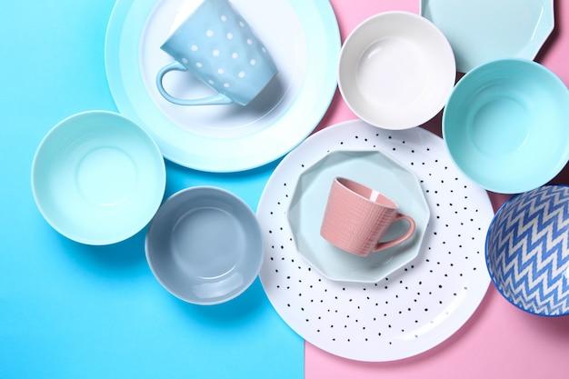 Set van verschillende moderne witte en blauwe borden, kommen en kopjes op roze en blauw. Premium Foto