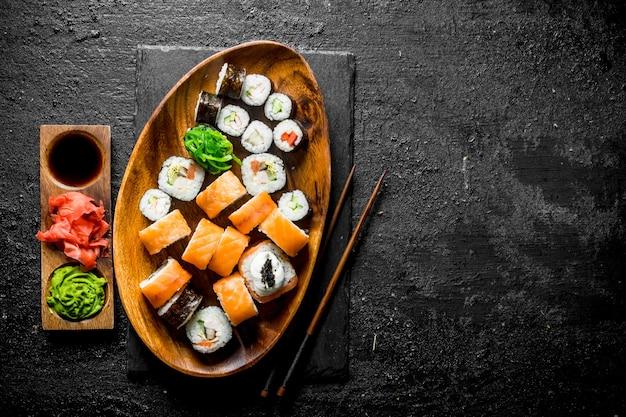 Set van verschillende sushi rolt met gember, sojasaus en wasabi op zwarte rustieke tafel Premium Foto