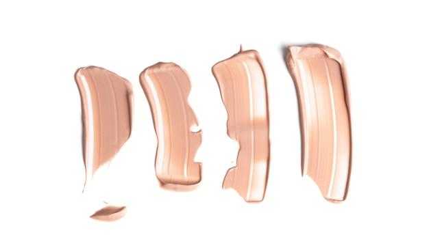 Set van zacht beige uitstrijkjes van make-up romige foundation geïsoleerd op een witte achtergrond. cosmetische camouflagestift. realistische bruine crèmetextuur voor make-up. Premium Foto