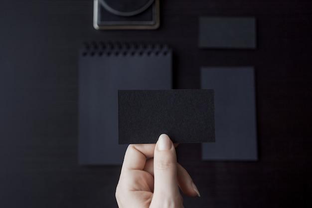 Set van zwarte mockups op donkere, vrouwelijke hand met een visitekaartje Premium Foto