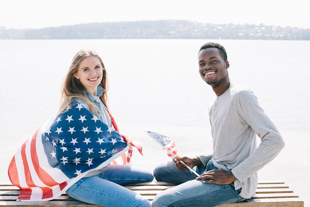 Sex tussen verschillendre rassen patriottische paarzitting op bank Gratis Foto