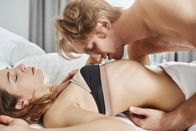 Sexy aantrekkelijke vriendin dragen van erotische lingerie liggend in bed met knappe jongen terwijl hij haar aanraakt en kust tijdens sensueel voorspel in de ochtend. seksueel aangetrokken paar in de slaapkamer Gratis Foto