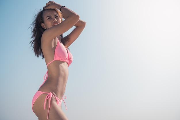 Sexy bikini lichaam vrouw zonnebril ontspannen op perfect tropisch strand en turkoois oceaan water. onherkenbaar model in mode zwemkleding met gladde bruine huid. Gratis Foto