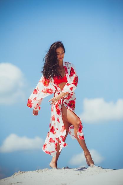 Sexy bikinilichaam vrouw die zich vrij voelt met een slanke buik en gladde dijen, gekleed in kleurrijke mode sjaal rok badmode strandkleding die pronkt met gewichtsverlies. laser beauty spa wellness-concept. Premium Foto