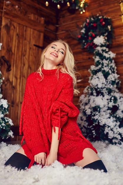 Sexy blondemeisje in rode sweater die pret in een ruimte met kerstmisdecoratie hebben Premium Foto