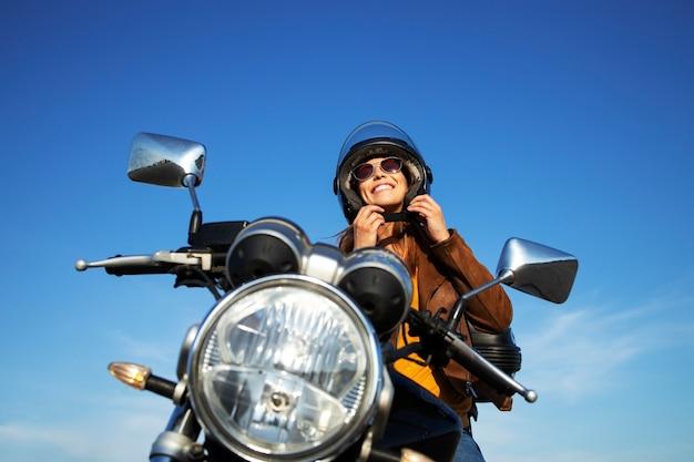Sexy brunette vrouw in leren jas helm zetten en zittend op retro stijl motorfiets op mooie zonnige dag Gratis Foto