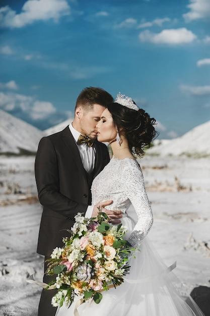 Sexy en mooi brunette model meisje met stijlvol kapsel en met diadeem, in witte kanten jurk en stijlvolle knappe mannen in trendy pak poseren samen buiten op zouten woestijn Premium Foto