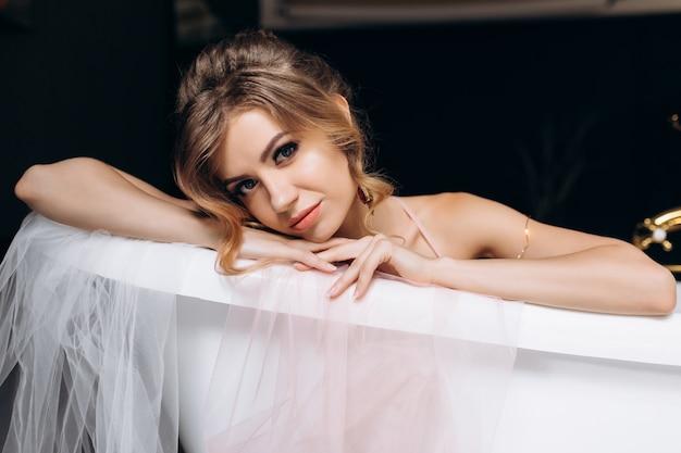 Sexy jonge blonde in sprankelende lingerie ligt in de badkamer bedekt met zijde Gratis Foto