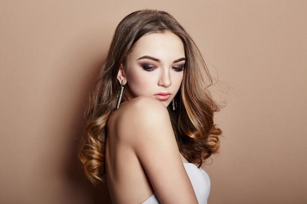Sexy jonge blonde meisje haar sieraden oorbellen in haar oren Premium Foto