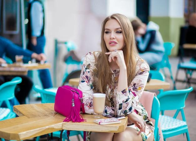 Sexy jonge hipster stijlvolle vrouw zitten in café, lente zomer modetrend, koffie drinken Gratis Foto