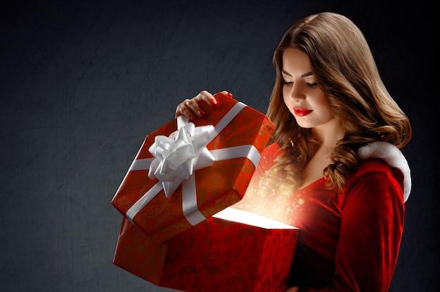 Sexy jonge vrouw in rode pak van de kerstman met geschenken. op een da Gratis Foto