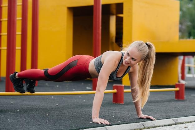 Sexy meisje dat duw-ups in openlucht doet. fitness. gezonde levensstijl Premium Foto