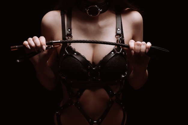 Sexy meisje in een zwarte mooie beha spelen met een zweep. het concept van bdsm Premium Foto